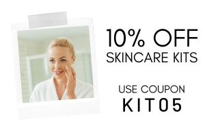 Woman applying cream in the mirror with 10% off skincare kits